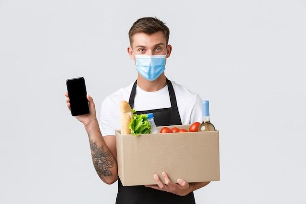 Covid koncepcja zakupów zbliżeniowych i dostawy artykułów spożywczych przystojny sprzedawca w masce medycznej sugeruje ...
