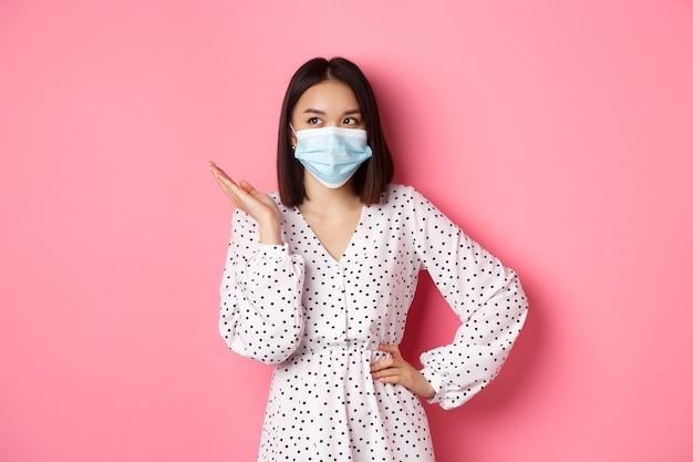 Covid kwarantanna i koncepcja stylu życia urocza azjatycka kobieta w masce na twarz podnosząca rękę stojąc w sukience...