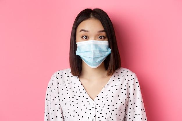 Covid pandemia i koncepcja stylu życia zaskoczyła azjatycka kobieta w masce na twarz unosząca brwi, wpatrująca się w ...