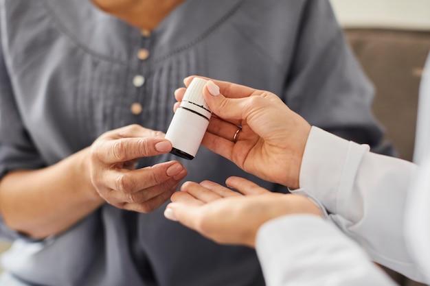 Covid recovery center kobieta lekarz rozdający butelkę pigułek dla starszego pacjenta
