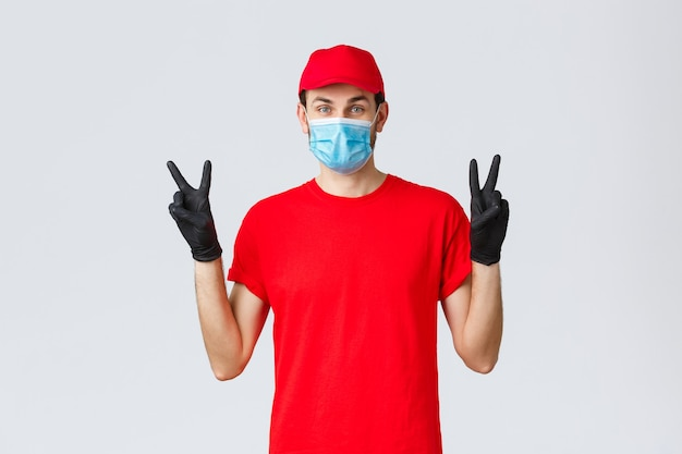 Covid samodzielna kwarantanna online zakupy i wysyłka koncepcja słodki facet dostawy w czerwonej jednolitej masce na twarz...