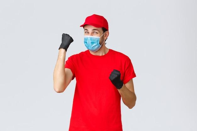 Covid samodzielna kwarantanna zakupy i wysyłka online koncepcja wesoła dostawa mężczyzna w czerwonej jednolitej rękawiczce...
