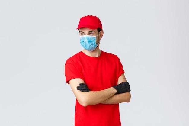 Covid samodzielna kwarantanna zakupy online i koncepcja wysyłki pewny siebie kurier w czerwonym mundurze ochronnym...