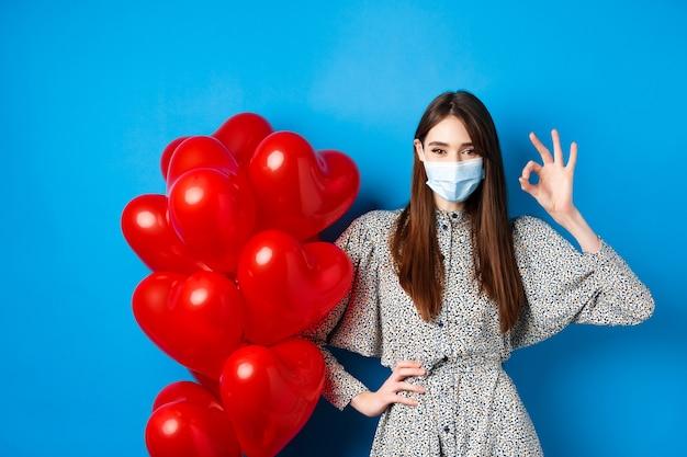 Covid walentynki i koncepcja pandemii piękna młoda kobieta w masce na twarz i sukience pokazująca ok si...