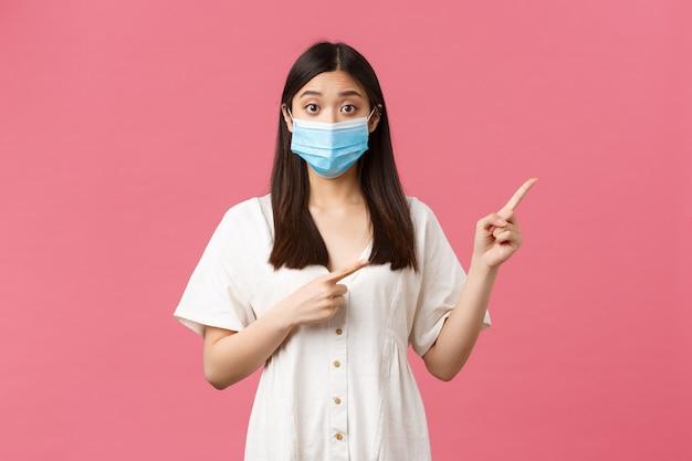 Covid wirus dystansu społecznego i koncepcja stylu życia zaintrygowała urocza azjatycka kobieta w masce medycznej pyta...