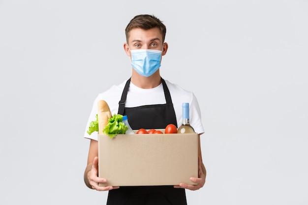 Covid zakupy zbliżeniowe i koncepcja dostawy artykułów spożywczych przystojny przyjazny sprzedawca kurier w medy...