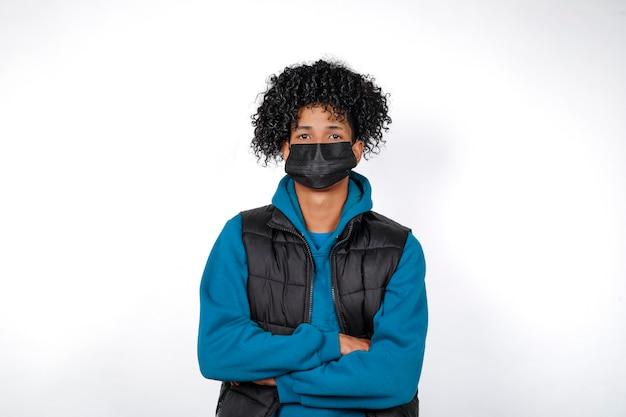 Covid19. zamknięty frontalny portret przypadkowy afro młody człowiek ubrany w czarną maskę medyczną na białym tle na białym tle. młody mężczyzna afro patrząc w kamerę.