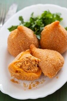 Coxinha de frango, typowy brazylijski krokiet z kurczaka na białym talerzu