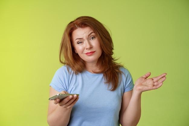Cóż, meh obojętny beztroski wahający się rudy kobieta w średnim wieku dojrzała czerwona kobieta wzruszająca ramionami trzymaj smartfon uśmieszek znudzony niezainteresowany trzymaj rękę na boku apatyczna postawa zielona ściana