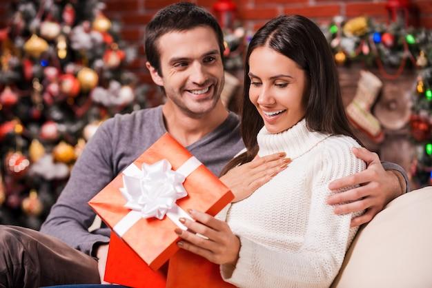 Cóż za niespodzianka! piękna młoda kobieta otwiera pudełko z prezentami i uśmiecha się, podczas gdy jej chłopak siedzi blisko niej na kanapie ze świąteczną dekoracją w tle