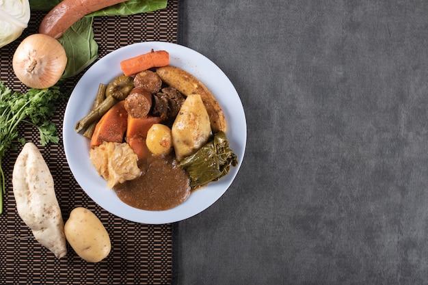Cozido to danie brazylijskiego jedzenia na szarym stole i widok z góry.