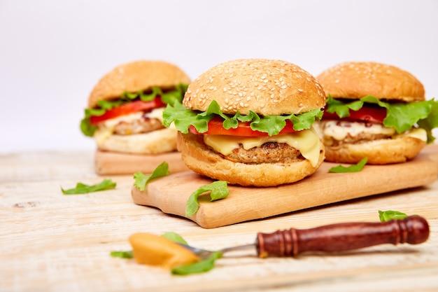 Craft burger wołowy na drewnianym stole na jasnym tle.