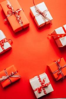 Craft pudełko z czerwoną wstążką na czerwonym tle. boże narodzenie i nowy rok tło wakacje