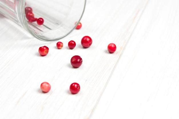 Cranberries w drewnianym pucharze na biel powierzchni