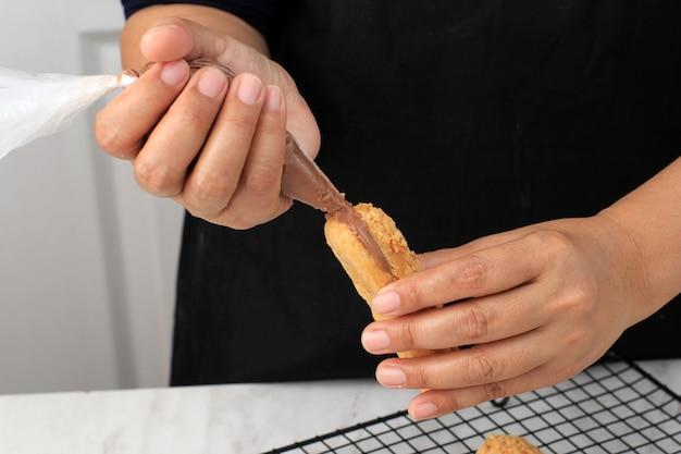 Craqueline eclair z nadzieniem z kremem czekoladowym. azjatycka kobieta trzyma worek ciasta (plastik segitiga). domowe wypieki przygotowanie pieczenie ciasto parzone/ptyś z kremem.