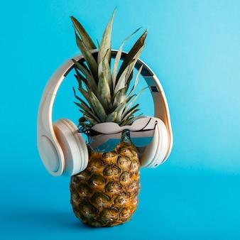 Creative śmieszne ananas twarz nosi okulary przeciwsłoneczne słuchawki. ananasowa twarz lewitujący słuchanie muzyki na tle niebieskiego lata. kwadrat wysokiej jakości pień fotografia.