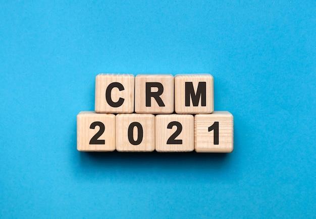 Crm - koncepcja tekstu na drewnianych kostkach z gradientowym niebieskim tłem.