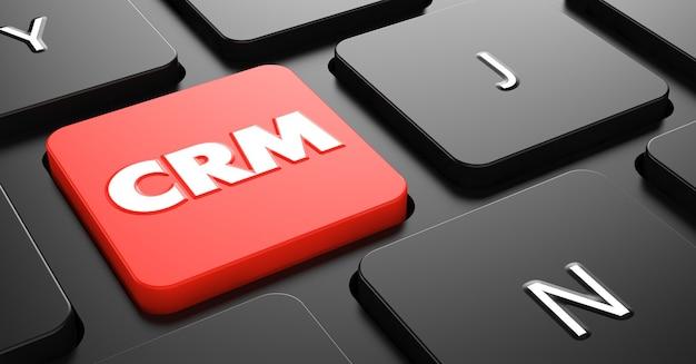 Crm na czerwony przycisk na czarnej klawiaturze komputera.
