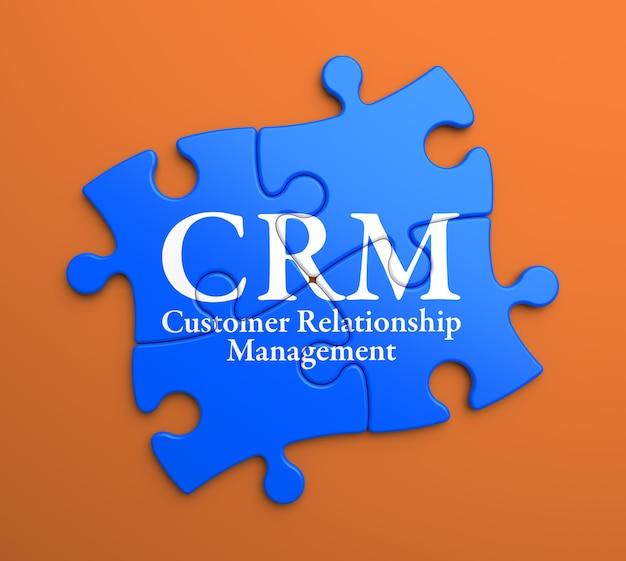 Crm - zarządzanie relacjami z klientami - napisane na niebieskich puzzlach. pomysł na biznes.