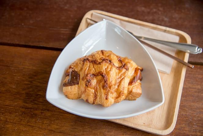 Croissant baleronu ser na białym naczyniu i drewno talerzu z drewnianym tłem.