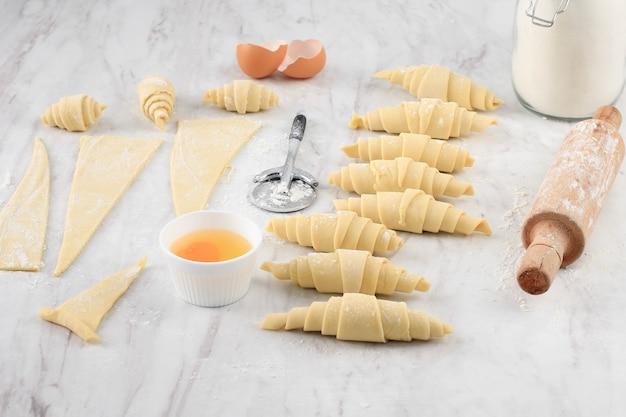 Croissant domowej roboty, surowy croissant do wypieku w domu. rogalik w różnych rozmiarach nad stołem z białego marmuru