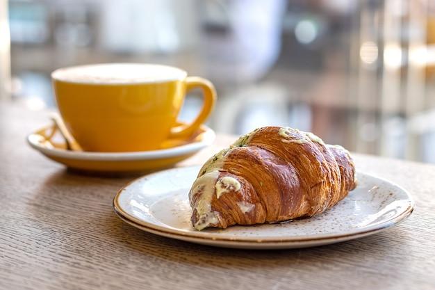 Croissant i cappuccino w żółtej czapce na drewnianym stole w kawiarni