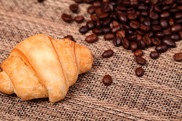Croissant i świeże kawowe fasole na drewnianym stole