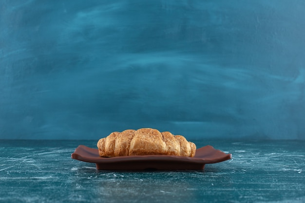 Croissant na brązowym talerzu, na niebieskim stole.
