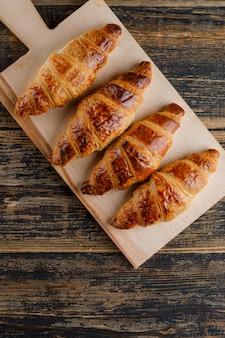 Croissant płaski leżał na drewnianej desce do krojenia