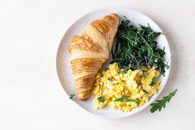 Croissant podawany z jajecznicą i szpinakiem na talerzu. śniadanie.
