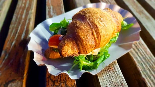 Croissant z awokado, pomidorem i ziołami na zewnątrz. uliczne wegetariańskie jedzenie.