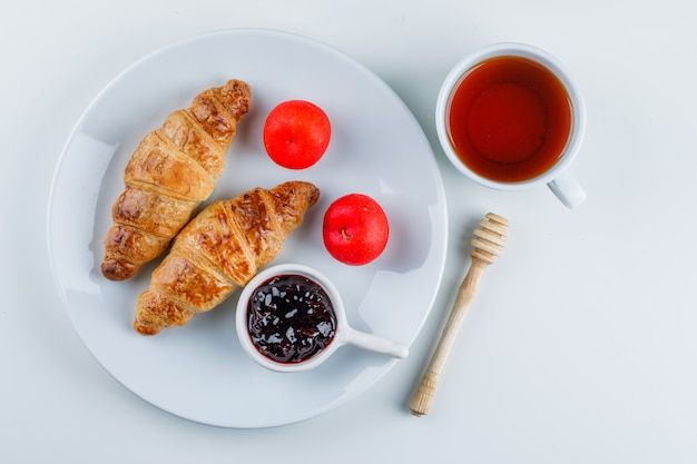 Croissant z dżemem, śliwkami, dipem, herbatą na talerzu, leżak na płasko.