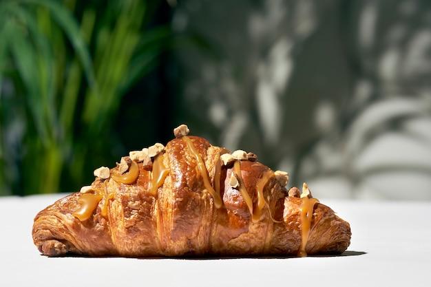 Croissant z karmelem i orzechami. ostre światło. białe tło. tekstura, zbliżenie, selektywne skupienie