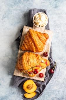 Croissant z nektaryną, wiśnią i ricottą lub serkiem śmietankowym na drewnianej desce do krojenia. widok z góry.