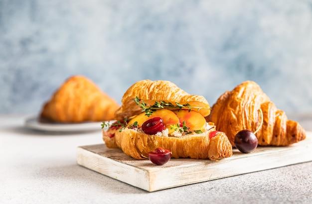Croissant z nektaryną, wiśnią i ricottą lub serkiem śmietankowym na drewnianej desce do krojenia.