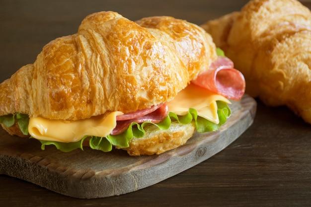 Croissant z serem kiełbaską i ziołami. na ciemnym tle