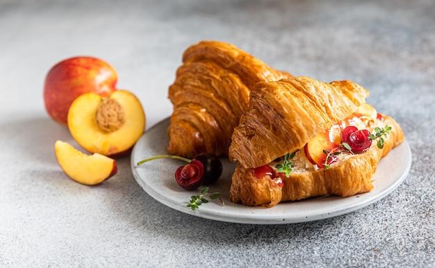 Croissant z serem nektarynka, wiśnia i ricotta, szary kamień tło. smaczne śniadanie.