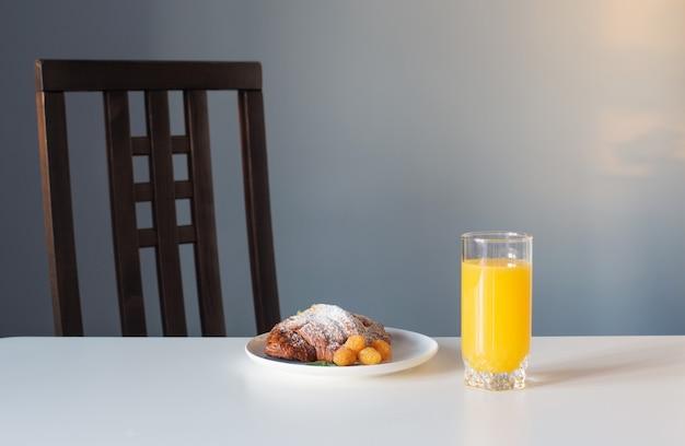 Croissant z sokiem pomarańczowym na białym stole