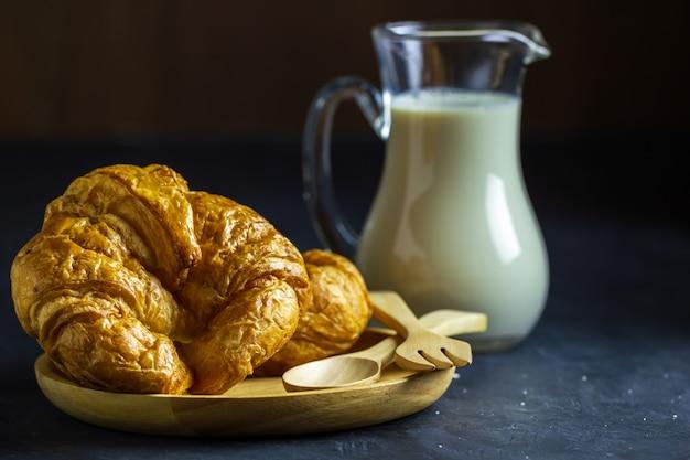 Croissants na drewnianym naczyniu i dojnym dzbanku na stole w ciemnym tle.