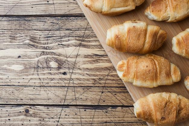 Croissants z czekoladowym plombowaniem na drewnianym tle. skopiuj miejsce