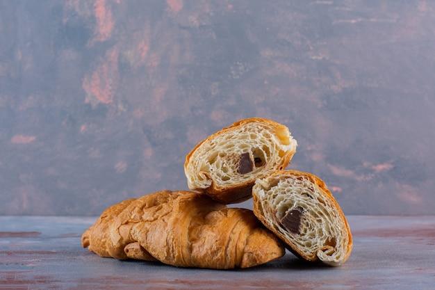 Croissanty w całości i krojone na marmurowym tle.