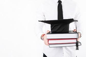 Crop Alumnus z książkami i czapką