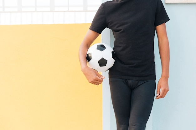 Crop black man standing and holding football