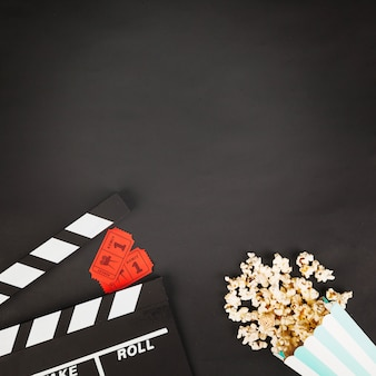 Crop clapperboard w pobliżu biletów i popcorn