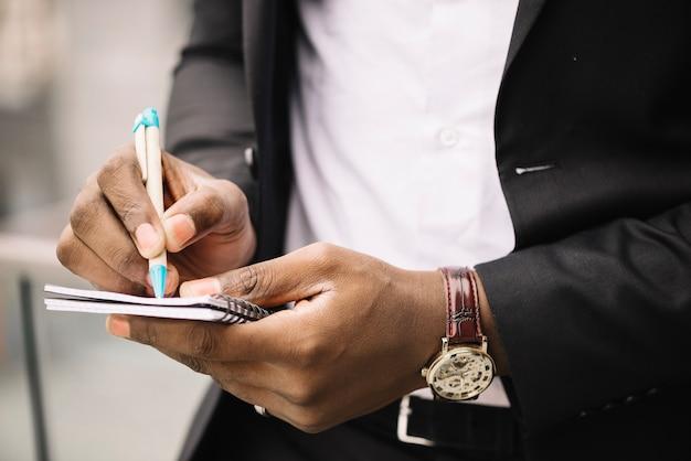 Crop człowiek pisze notatkę