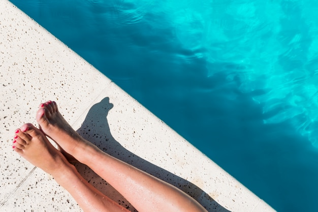 Crop female legs on poolside