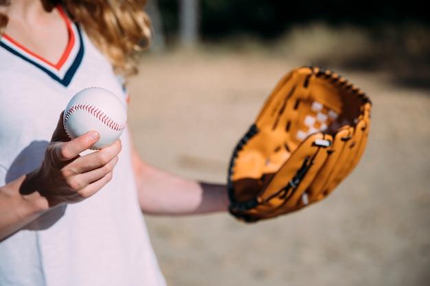 Crop female utrzymuje baseball i rękawicę