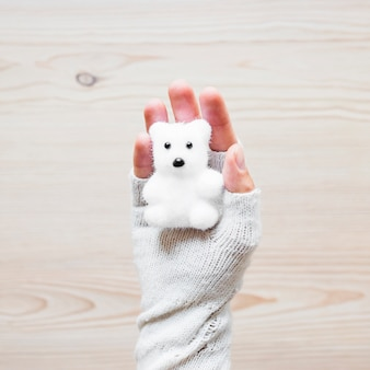 Crop hand with toy bear