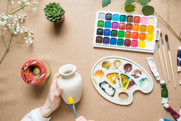 Crop hands painting vase