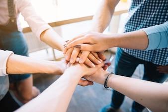 Crop kolegów trzymając się za ręce razem